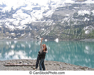 A woman and a jumping man on a mountain lakeshore,...