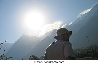 A trekker man with a hat starting his day by a clear sunny weather, Chamonix, The Alps mountain, France