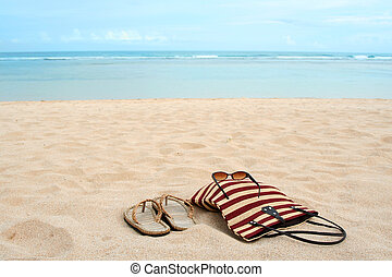 Beach vacation - A pair of sandals and sunglasses on a sandy...