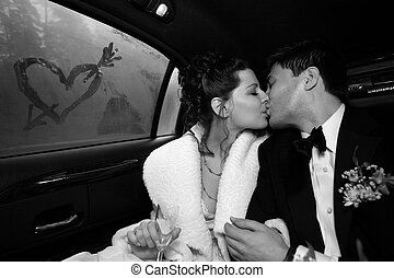 Kiss - The groom and the bride kiss in the car. On glass...