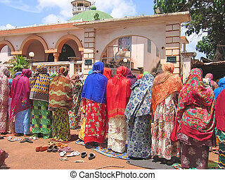 African woman praying with colored tissus, Cameroon, Africa...