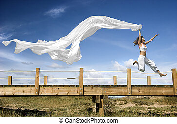Jumping with a scarf - Young beautiful woman jumping with a...