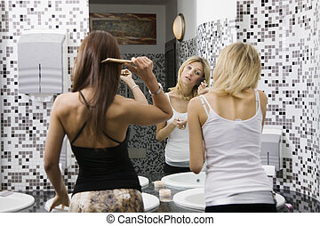 girls night out: girls applying makeup in the bathroom of a...