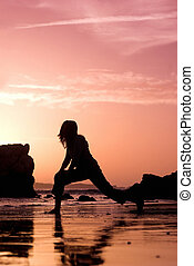 Sunset activities - Woman doing exercise on the beach