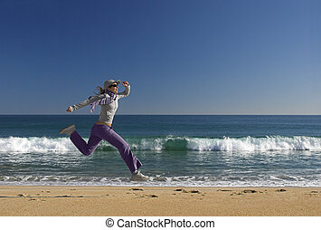 Jumping on the beach - Young woman jumping for fun in a...