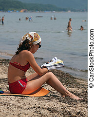 young girl reading on the beach