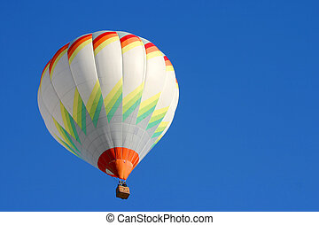 Hot air balloon in flight isolated on blue sky