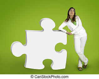 Woman contemplating questions with 3D puzzle form on a green...