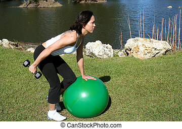 Triceps Kickbacks - woman at a park doing triceps kickbacks...