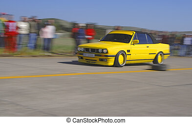 Yellow racing car - Panning image of a speedy car during a...