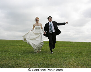 bride and groom running on meadow