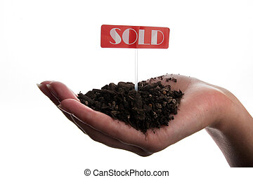 Sold land in hand - Sold sign and soil in hand isolated on...