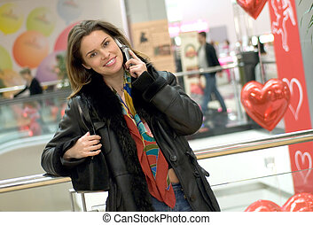 Woman talking by mobile phone in shopping marketplace -...