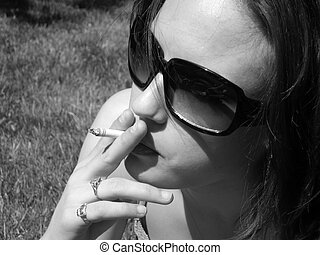 Smoker - Attractive model out in the sun Wearing sunglasses...