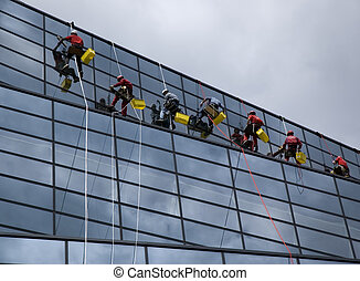 wash - Window washers high above the city silhouette