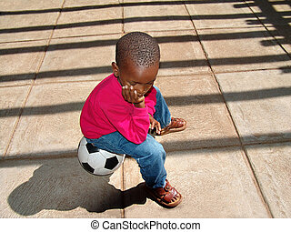 Waiting - African American child sitting on the ball waiting...