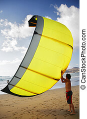 Kitesurfing - Kitesurfer getting ready to go out with yellow...