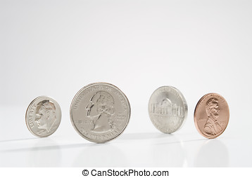 four coins standing on end, white surface with slight shadow...