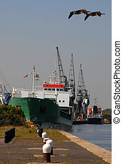 Cargo Ship - Cargo ship at the quayside unloading with...
