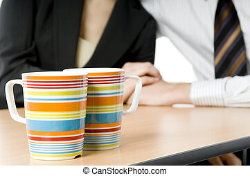 Office Romance - A pair of colorful coffee cups in focus...