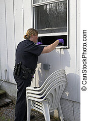 Police dusting for prints - Police woman dusting for finger...