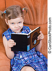 Little girl reading book and smirk