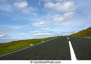 The Open Road - Steep uphill road, free of cars, with grass...