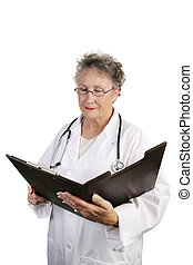 Mature Female Doctor Reviewing Chart - A mature female...