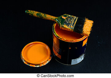 can of yellow paint with brush