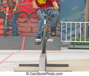 BMX rider on a balance beam during a competition