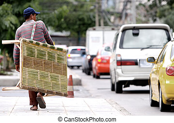 Homeless guy walking on the street with bed at his side.