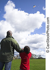 father and son flying kite together