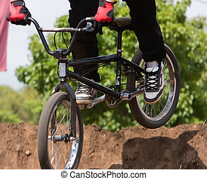 BMX Biker - A BMX Bicycle Moto-crossX going over a dirt...