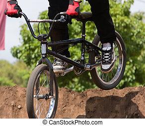 BMX Biker - A BMX (Bicycle Moto-cross(X)) going over a dirt...