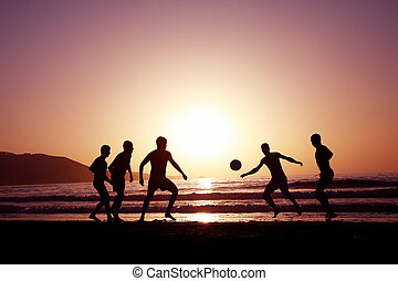 Sunset Football - A game of football on the beach at sunset