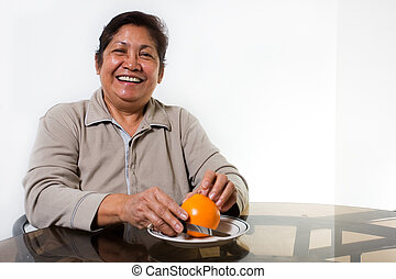 Orange for breakfast - Portrait of a senior asian woman...