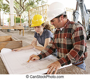 Engineer and Student Review Plans - An engineer and a female...