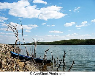 fishermans boat on the shore of a lake