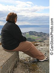 Obese woman - Depressed obese woman sitting on a mountian...