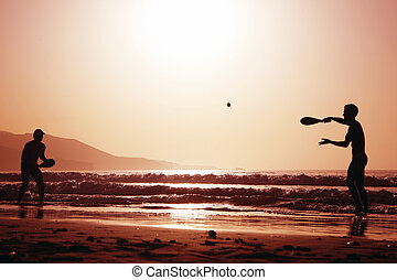 Sunset Tennis - Two men playing beach tennis on the beach