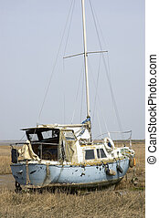 Stuck in the mud - A small yacht in the mud at low tide