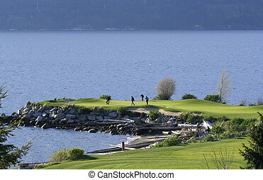 Water Hazard - A group of golfers on a green by the sea.