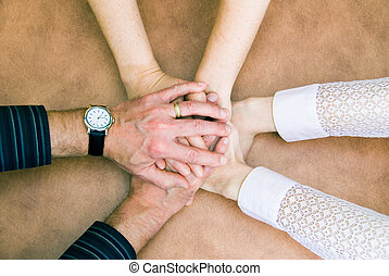 Teamwork - six hands clasp together in symbol of unity