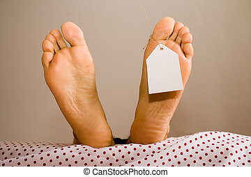 Dead feets - dead foots with a white tag in a bed