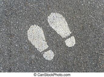 Painted footprints on asphalt