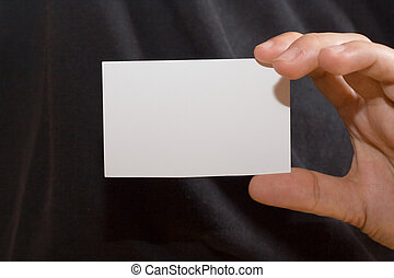 White card on black - A hand showing a white card, with a...