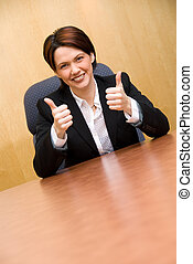 2 thumbs up - happy business woman in a boardroom table