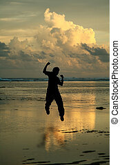 Happy man - A happy man jumping in the air on the beach, in...