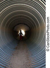 In the Culvert - Child walking in a culvert under the road