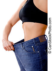 losing weight - female wearing old jeans who has lost weight